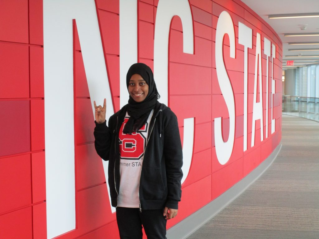 Student Stands by NC State wall in Talley Student Union