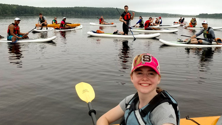 Students kayak on a lake during Outdoor Adventures Program