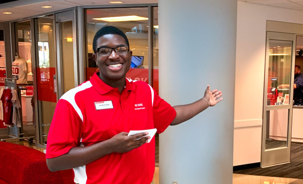 Student Leader Smiles and welcomes families and students during orientation